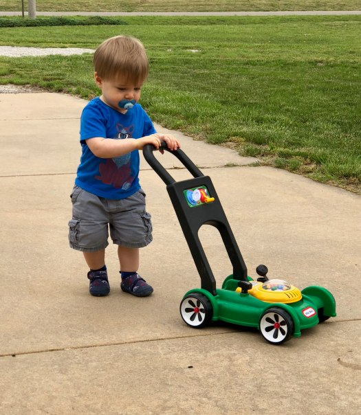toddler mowing the driveway