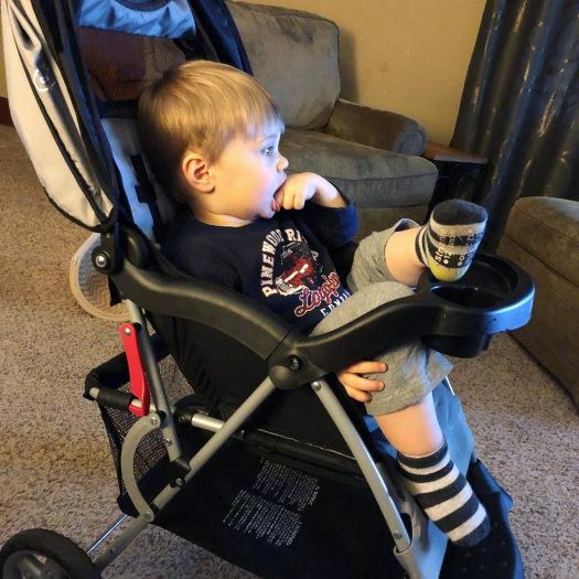 toddler climbs himself into stroller
